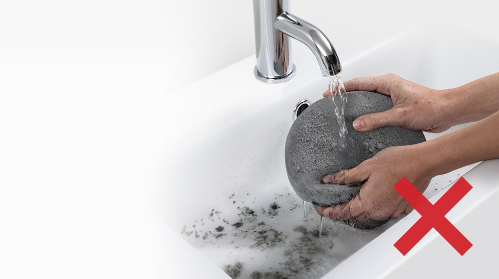 A dirty, dust-clogged filter being washed in the sink.